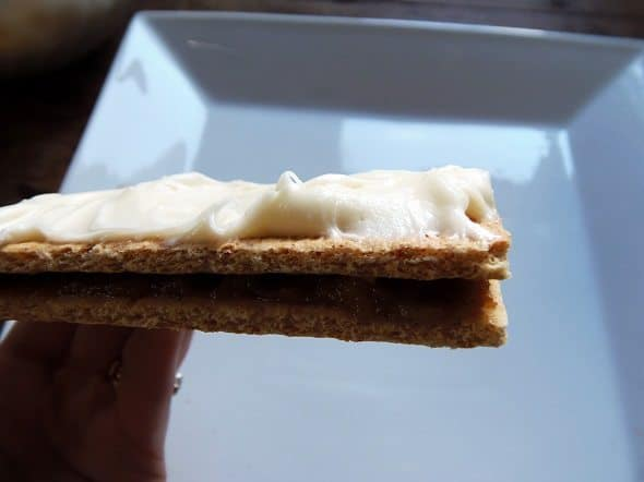 Spread Cream Cheese Frosting on Cracker