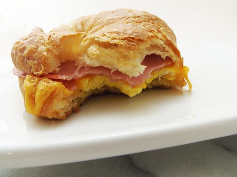 Ham, Egg and Cheese Croissant With Bites Taken Out of It
