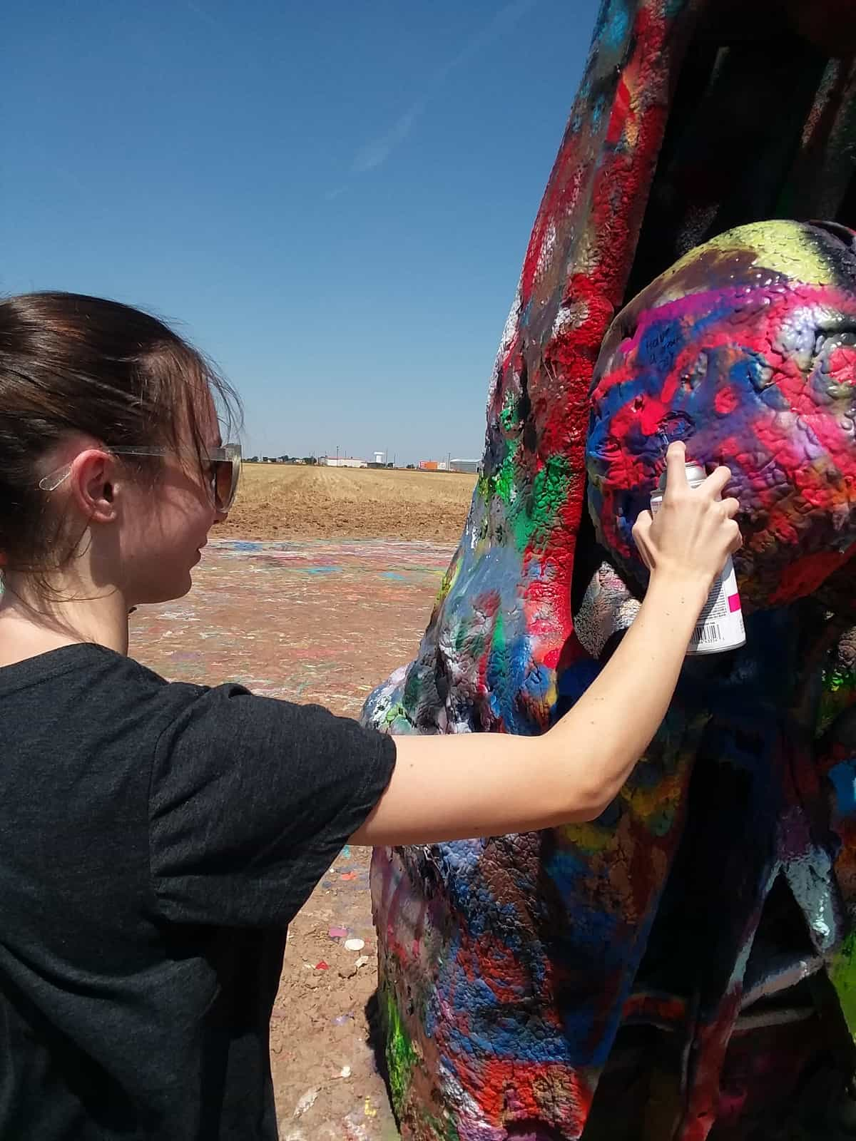 Oldest Daughter Spray Painting Car at Cadillac Ranch