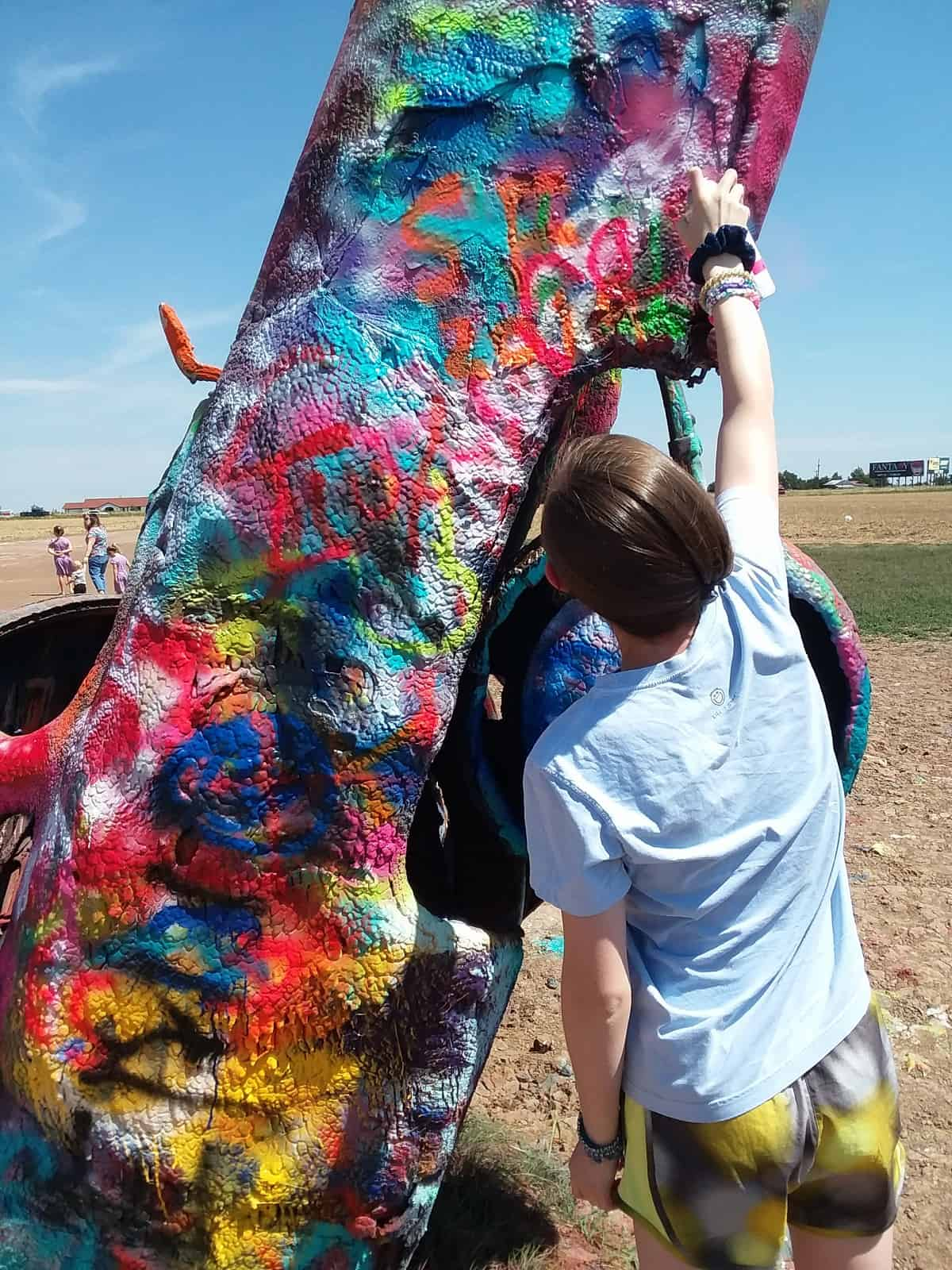 Youngest Daughter Spray Painting Car at Cadillac Ranch